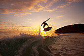 Hawaii, Maui, Makena, Skimboarder gets big air off a wave at sunset