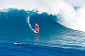 Hawaii, Maui, Peahi (Jaws), Windsurfer rides large wave and jetskier in foreground