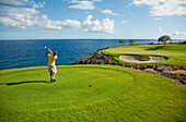 Hawaii, Lanai, Man playing golf at The Challenge at Manele Golf Course.