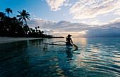 French Polynesia, Moorea, Woman paddling in outrigger canoe along shoreline.