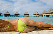 French Polynesia, Tuamotu Islands, Rangiroa Atoll, Woman lounging on beach, Luxury resort bungalows in background, View from behind.