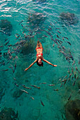 School of fish encircling woman floating in tropical ocean water.