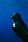 Hawaii, Big Island, Honaunau Bay, Young woman exhales as she swims to the surface.
