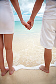 Hawaii, Oahu, Young engaged couple facing the beach holding hands, view from behind