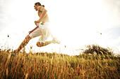Hawaii, Oahu, Atheltic Male jogging on an outdoor field walkway path