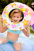Hawaii, Oahu, Young girl playing in a pool with an innertube.