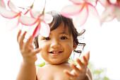 Hawaii, Oahu, Baby girl playing with plumeria flowers.