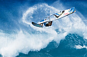 Hawaii, Maui, Ho'okipa, Professional windsurfer Marcilio Browne catches big air off wave. FOR EDITORIAL USE ONLY.