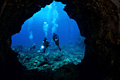 Hawaii, Lanai, Divers pictured at the entrance to a lava tube