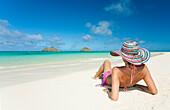 Hawaii, Oahu, Lanikai Beach, Woman relaxing along sandy shore.