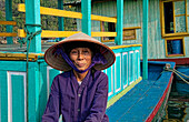 South East Asia, Vietnam, Ha Long Bay, Portrait of a Vietnamese woman sitting on docked fishing boat.