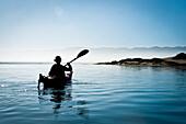 California, Morro Bay State Park, Woman kayaking in ocean, silhouette.