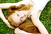 Young woman with freckles and red hair lays in the grass and looks up.