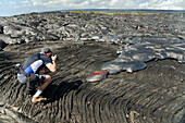 Hawaii, Big Island, Kalapana, Man photographs Pahoehoe lava flowing from Kilauea covering an older Pahoehoe flow.