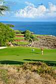 Hawaii, Lanai, Woman putting on green at The Challenge at Manele golf course.