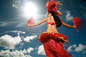 Hawaii, Kauai, Kealia, Beautiful Hawaiian girl dancing hula on ocean shoreline.