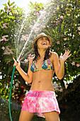 Hawaii, Oahu, Young girl splashing water on herself with hose.