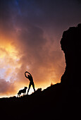 Hawaii, Silhouette of a woman stretching on a mountain top at sunset.
