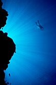 Micronesia, Yap, Light rays shining through reef canyon, Diver in distance.