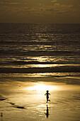 Indonesia, Bali, Semniyak, Silhouette of young boy running on the beach.