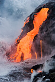 Hawaii, Big Island, near Kalapana, Pahoehoe lava flowing from Kilauea into Pacific Ocean, Seaspray and steam in air.