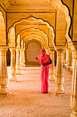 India, Rajasthan, Jaipur, Amber Fort Temple, woman in bright pink sari stands beneath arches.