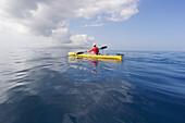 Hawaii, Maui, Man in yellow kayak along the calm ocean of the Southern coast.