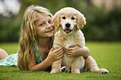 Hawaii, Maui, little girl sits on grass holding a golden retriever puppy.