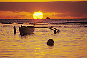 Hawaii, Outigger canoe silhouetted on ocean at sunset, orange reflections on water and sun on horizon.