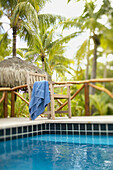 French Polynesia, Tahiti, Bora Bora, Deck chair with towel hanging over it next to swimming pool, tropical vegetation, selective focus