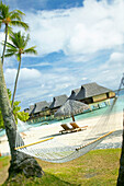 French Polynesia, Tahiti, Bora Bora, hammock in foreground of lounge chairs and thatch umbrella on beach with tranquil ocean and bungalows