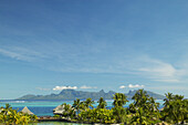 French Polynesia, Tahiti, View of Moorea across turquoise ocean, palm trees and grass huts in foreground