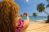 Hawaii, Oahu, Beautiful young woman photographing tropical beach with lei.