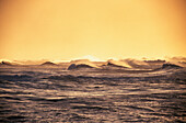 Hawaii, Sunset light on dark blue ocean with stormy surf, rough waters.