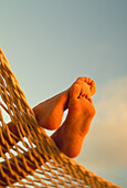 Close-up of bottom woman's feet crossed, hammock with golden afternoon light, sand