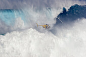 Hawaii, Maui, Helicopter filming tow-in surfer at Peahi aka Jaws, Wild crashing waves.