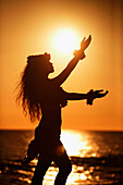 Hawaii, Oahu, Silhouette of Hawaiian hula dancer next to the ocean at sunset.