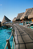 French Polynesia, Moorea, Wooden walkway over crystal water leading to water bungalows