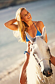 Hawaii, Blonde Caucasian woman riding white horse on beach
