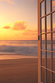Afternoon beach scene open door along shoreline, golden clouds shore break waves hues D1632