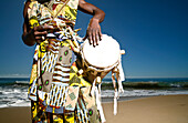 Hawaii, Kauai, Kealia Beach, African Dancer with drum on shore.