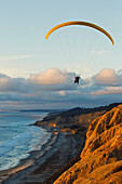 California, La Jolla, Paraglider flying over ocean cliffs at sunset. EDITORIAL USE ONLY.