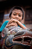 'Young Boy Leaning On Stone Dragon Head; Bhaktapur, Nepal'