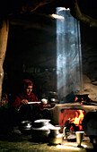 'A Gujjar Woman Makes Salt Tea In Her Hut As A Shaft Of Light Beams Down Through The Smoke; Kashmir India'