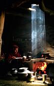 'A Gujjar Woman Makes Salt Tea In Her Hut As A Shaft Of Light Beams Down Through The Smoke; Kashmir India'
