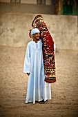 'A Muslim Man Carrying A Rolled Persian Rug; Nubia Egypt'