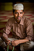 'Portrait Of A Young Man Wearing A Prayer Cap With His Prayer Beads; Singapore'