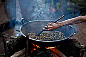 'Hand Stirring Coffee Beans Over Fire; Muara Pinang Indonesia'