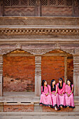 'Four Young Women Wearing Pink And Sitting On A Ledge; Bhaktapur Nepal'