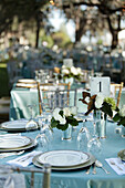 A formal party dining table laid out on a lawn under shady trees with glasses, silver flatware and candles. Evening. A gala party., Savannah, Georgia, USA, Outdoor Party